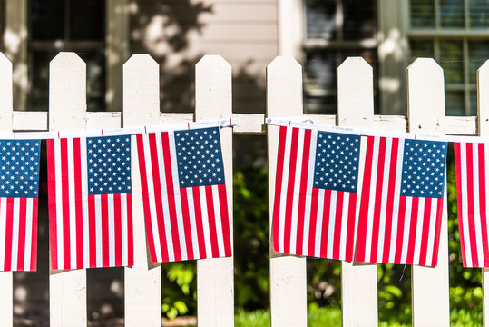 Patriotic American flags hanging decorations on white picket fence in Aspen, Colorado near Independence Day July 4th celebration
