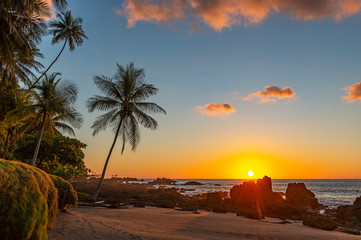 Sunset along the volcanic rock beach of Corcovado national park with a sunbeam by the Pacific Ocean, Costa Rica, Central America. Fototapete