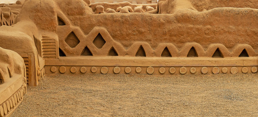 Panorama of the adobe walls and decorations in the archaeological site of Chan Chan made by the Chimu civilization near Trujillo, Peru.