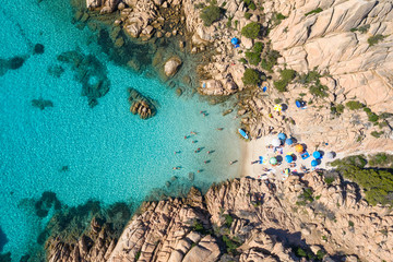 View from above, stunning aerial view of a small beach with beach umbrellas and people swimming in a turquoise clear water, Cala Coticcio, (Tahiti), La Maddalena Archipelago, Sardinia, Italy.