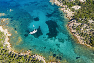 Wall Mural - View from above, stunning aerial view of a sailboat floating on a beautiful turquoise sea that bathes the green and rocky coasts of Sardinia. Emerald Coast (Costa Smeralda) Italy