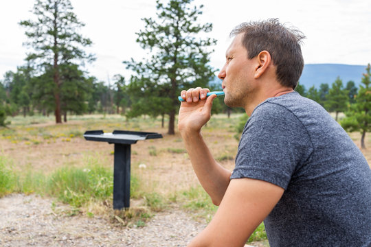 Campsite with man brushing teeth with toothbrush in morning on Canyon Rim Campground in Flaming Gorge Utah National Park