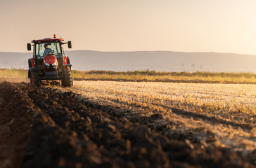 Tractor plowing fields in sunset