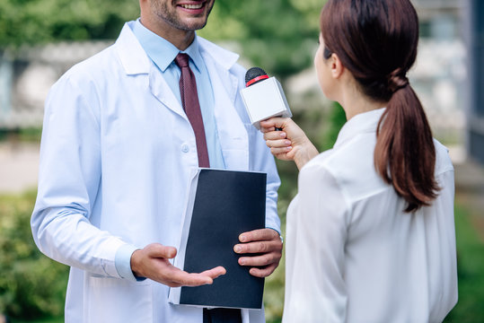 cropped view of journalist holding microphone and talking with doctor in white coat