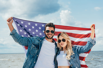 Fotomurales - attractive woman and handsome man smiling and holding american flag