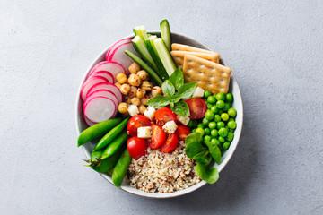 Healthy vegetarian salad. Buddha bowl. Grey stone background. Top view. Close up.