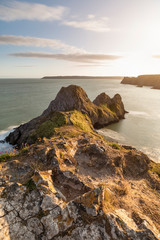 Spoed Foto op Canvas Chocoladebruin Beautiful peaceful Summer evening sunset beach landscape image at Three Cliffs Bay in South Wales