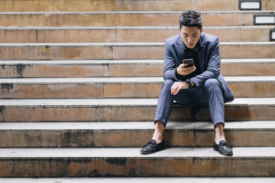Businessman sit on stair use mobile phone for social network organize, planning project, make appointment, business chat.