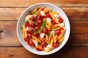 Pasta penne with roasted tomato, sauce, mozzarella cheese. Wooden background. Top view.