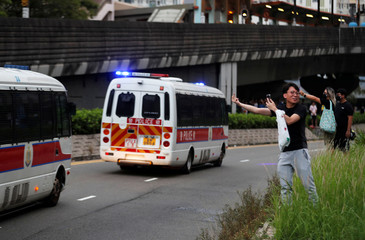 A demonstrator gestures towards passing police cars in Tin Shui Wai in Hong Kong