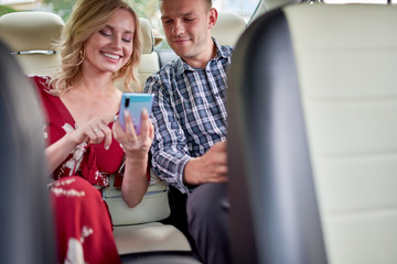 Image of happy blonde women and men with phone in hands sitting in back seat of car.