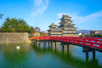 Wall Mural - View of Matsumoto Castle with red bridge in Nagano, Japan