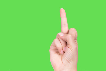 Poit of view close up view of one single middle finger raised up in rude gesture. Horizontal color photography of beautiful female hand isolated on green background.