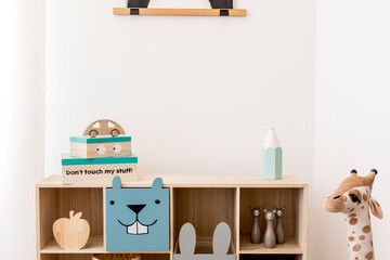 Stylish scandinavian child room with wooden cabinet, toys, boxes and plush teddy. White walls, Minimalistic home decor of playroom. Template. Copy space.
