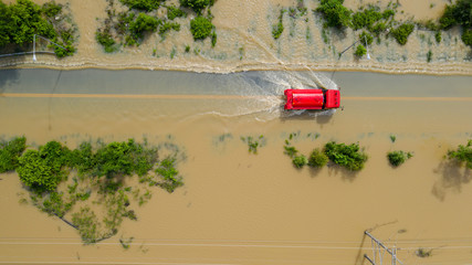 Aerial top view of Flooded the village and Country road with a red car, View from above shot by...