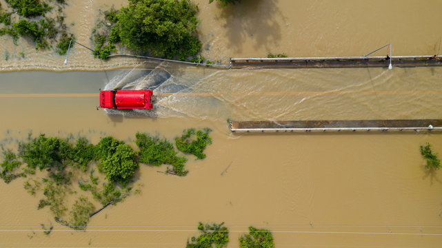 Aerial top view of Flooded the village and Country road with a red car, View from above shot by drone