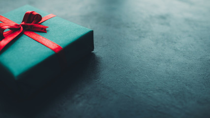 Birthday present. Cropped closeup of gift box with red ribbon bow on dark teal blue background. Copy space.