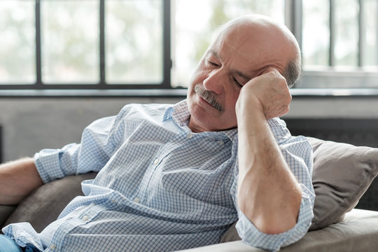 Tired senior hispanic man sleeping on couch, taking afternoon nap at the living room