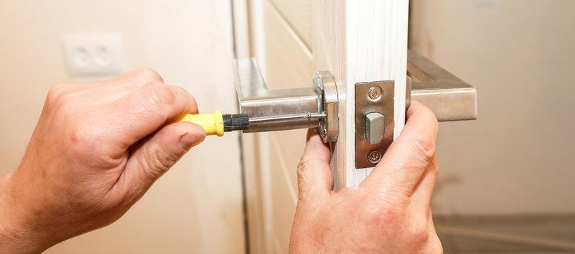 Man is installing the doors handle. Repair works. Maintenance in the apartment.