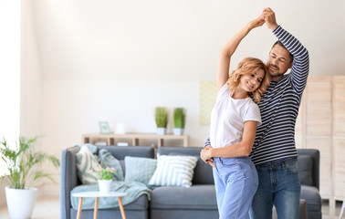 Happy dancing couple at home