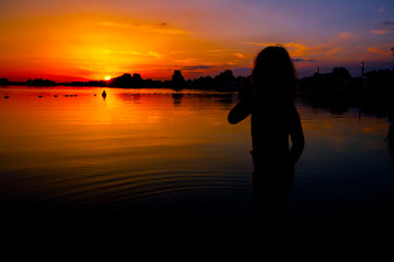Silhouette of child by the lake and the orange sky in sunset