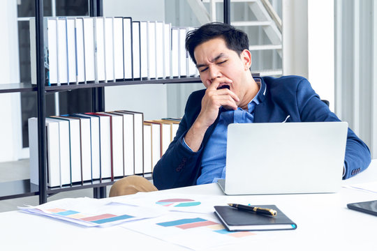 A young businessman sitting in a modern office. He has a feel sleepy because  hard work so tired weary fatigued and exhausted. On his table have a computer laptop tablet pen paper graph.