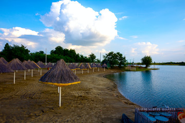 Empty sandy beach by the lake with thatched sunshades