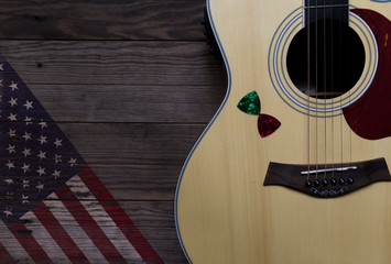 Acoustic guitar placed on an old wooden table, With a picture of an American flag on wood, Close-up