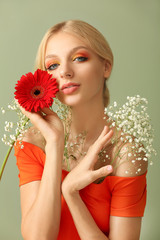 Beautiful young woman with flowers on color background
