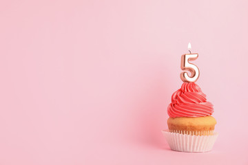 Birthday cupcake with number five candle on pink background, space for text