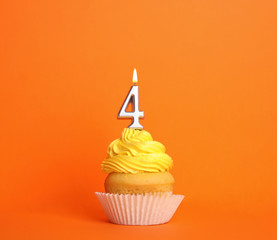 Birthday cupcake with number four candle on orange background