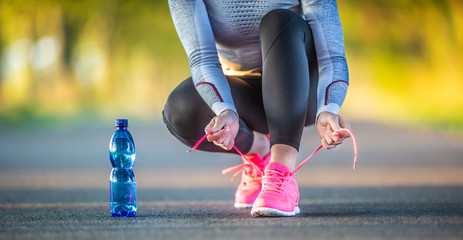 Woman runner tying shoelaces before jogging in autumn tree alley park. Sports female autumn outfit leggings and thermal underwear.