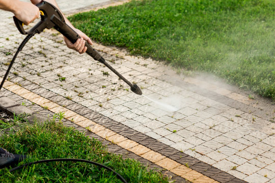 Close up photo of a man hands, cleans a tile of grass in his yard. High pressure cleaning