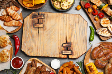 Frame of barbecued meat and vegetables on grey table, flat lay. Space for text Wall mural