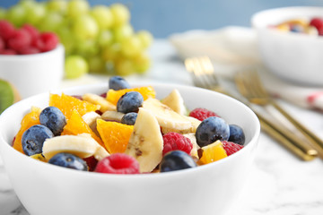 Fresh tasty fruit salad on white marble table, closeup