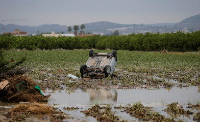 An overturned damaged car is stranded on a field after a flood caused by torrential rains in Orihuela