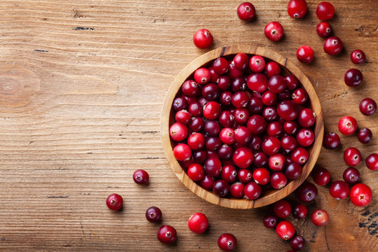 Ripe cranberry in wooden bowl on rustic table top view.
