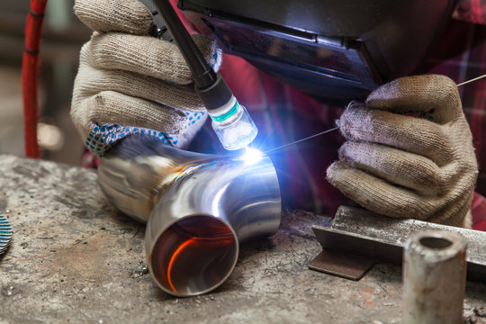 Young guy welder in a checkered red shirt welds a stainless steel pipe using agronomic welding to protect his eyes with a mask in an iron workshop. Modern welding methods.