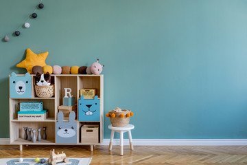 Stylish scandinavian newborn baby room with wooden cabinet, toys, children's chair, natural basket ...
