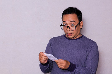an asian man raise the eyebrows and make it down his glasses while holding white mail paper.