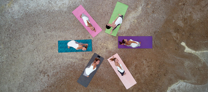 Aerial horizontal photography women do yoga performing Extended Triangle Pose outdoors