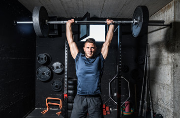 Young strong fit muscular sweaty man with big muscles doing heavy barbell weight lifting workout...