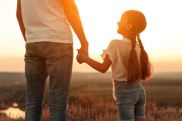 Happy daughter with father enjoying sunset in nature Wall mural