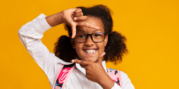 Smiling Black School Girl Looking Through Fingers Frame, Yellow Background