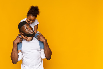 Cute african girl sitting on daddy's shoulders Wall mural