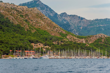 Luxury nautical vessels yachts motorboats mountains background Sea