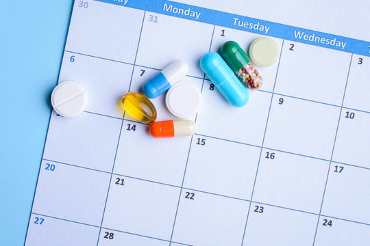 Pills on a calendar daily and weekly schedule