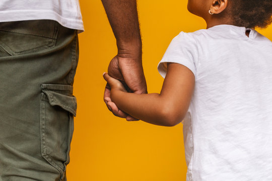 Little african girl holding her daddy hand and looking at him