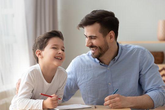 Happy dad and little kid son laughing drawing together