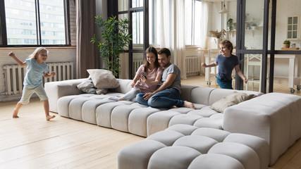 Joyful young parents sitting on sofa while kids running around.